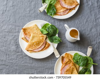 Crepes with ham and spinach. Delicious, nourish breakfast on a grey background, top view