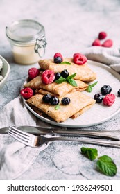 Crepes with homemade cottage cheese, raspberries a gray plate