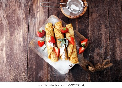 Crepes with jam, berries and sugar powder. Homemade pancakes, delicious breakfast.