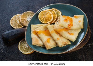 Crepes with orange jam and orange fruit chips served on a turquoise plate, studio shot on a dark brown stone surface