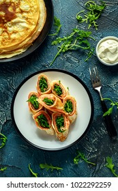 Crepes pancakes rolls with smoked salmon stuffed with wild rocket salad filling served on plate with fresh creme