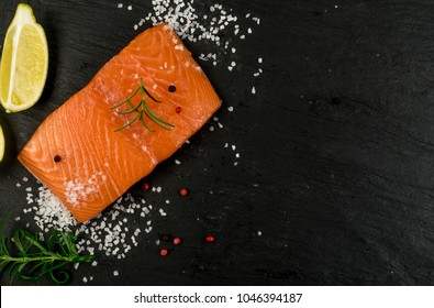 Crepes with Raw Sliced Salmon Fillet. Thick Pieces of Red Trout with Pancakes on Black Stone Background