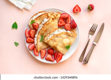 Crepes with ricotta cheese and fresh strawberries on pink pastel background, top view, copy space. Delicious crepes, thin pancakes.