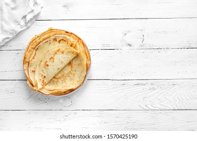 Crepes (Russian Blini) on white wooden background, top view, copy space. Homemade thin fresh crepes for breakfast or dessert.