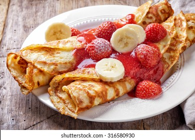 crepes with strawberries and banana on wooden table