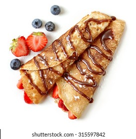 Crepes with strawberries and chocolate sauce isolated on white background