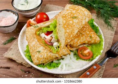 Crepes stuffed with Caesar salad, chicken, tomatoes, cheese and lettuce. Traditional Russian food.