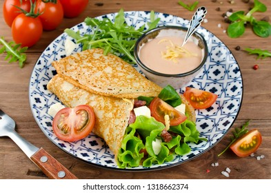 Crepes stuffed with salami, tomatoes, lettuce, mozzarella and cheese sauce. Traditional Russian food.