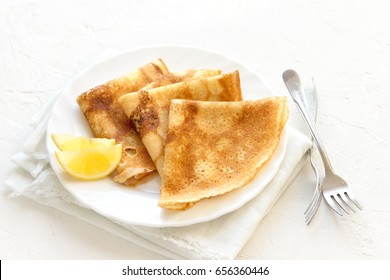 Crepes Suzette with lemon on white plate over white background, copy space. Delicious homemade Crepes for breakfast.
