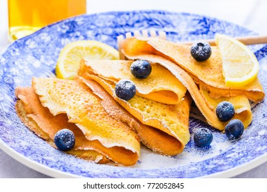 Crepes suzette served with berries. Delicious sweet breakfast with crepes or pancakes.