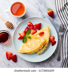 Crepes, thin pancakes with cream cheese, ricotta and fresh strawberries. Marble background. Top view.