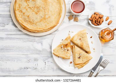 Crepes, thin pancakes with honey and nuts on a white plate . Wooden background .