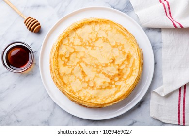 Crepes, thin pancakes with honey on a white plate. Marble background. Top view.