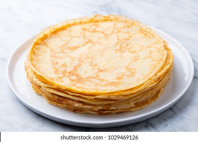 Crepes, thin pancakes with honey on a white plate. Marble background.