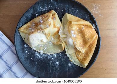 Crepes with vanilla ice cream and chocolate on dark stone plate