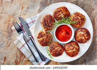 crepinette, fried flat sausages consisting of minced meat served on a  white plate, french cuisine, view from above, close-up