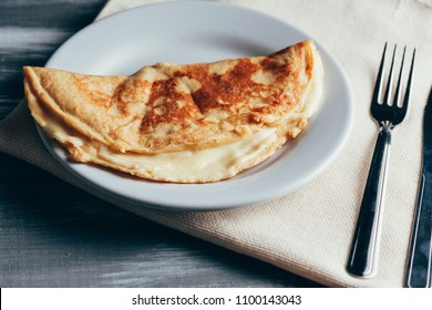 Crepioca - pancake of cassava (tapioca) with cheese on plate on wooden background. Selective focus