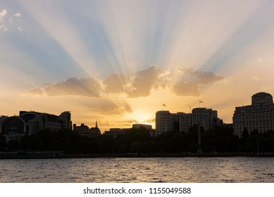 Crepuscular rays seen from the South Bank of the River Thames as the sun sets in London, UK in August 2018