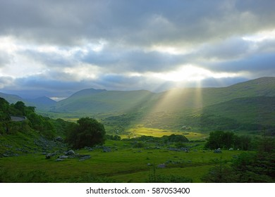Crepuscular Rays and soft evening sunlight on the beautiful Irish countryside looking towards Macgillycuddy's Reeks at Molls Gap, The Ring of Kerry, Co Kerry, Ireland