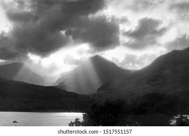 Crepuscular rays, speeding motor boat at sunset with low misty clouds covering the summit of Ben Vane and Ben Narnain, viewed across Loch Lomond from Inversnaid, Stirlingshire, Scotland