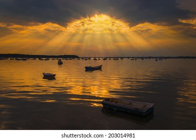 Crepuscular rays of sunlight shine onto still waters of Poole Harbour near Sandbanks, Poole, Bournemouth, Dorset