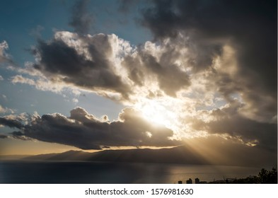 Crepuscular rays throught clouds over a mountain in golden hour