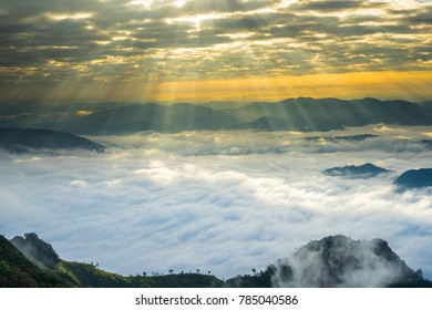 Crepuscular sun rays during sunrise over mist or foggy mountain at Phu Chi Dao Chaing Rai province, Thailand