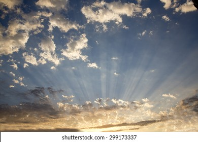 Crepuscular sun rays radiating through clouds