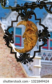 Crescent with a human face painted with gold paint - ornamental wrought iron decoration.
