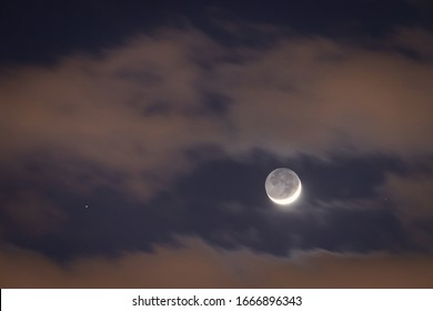 Crescent moon close approach to star. Earthshine is a soft, faint glow on dark side of moon; occurs when sunlight reflects off the Earth's surface and illuminates unlit portion of the Moon's surface.