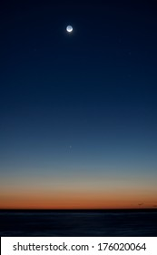 Crescent moon with detail in shadow during afterglow with Mercury visible above horizon.