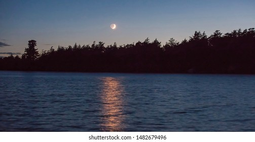 A crescent moon illuminated by the setting sun casts a golden glow over a northern Wisconsin lake.