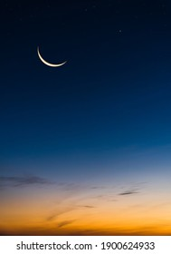 Crescent Moon on Twilight Sky in Evening Vertical with colorful sunlight after sundown,symbol Islamic Religion Ramadan, Dusk sky space background well for Arabic text present Eid al Adha, Eid al fitr.