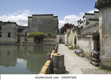 Crescent moon pond with bamboo laid on the wall to dry in the world heritage village of Hongcun, Anhui, China