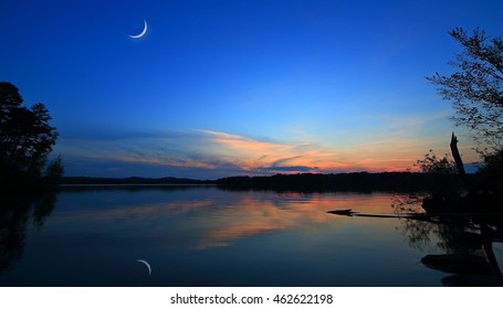 A crescent moon and its reflection over a shining Seneca lake, Ohio at sunset.