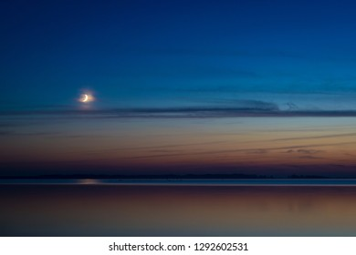 The crescent moon is setting over the Baltic Sea at dusk