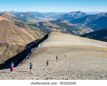 CRESTED BUTTE, COLORADO - SEPTEMBER 20, 2015: Hikers traverse the alpine terrain of the Ruby Range in the Elk Mountains high above Crested Butte, Colorado.