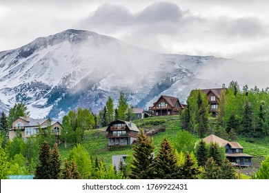 Crested Butte, USA Colorado town village in summer with clouds and foggy mist morning and houses on hillside with green trees