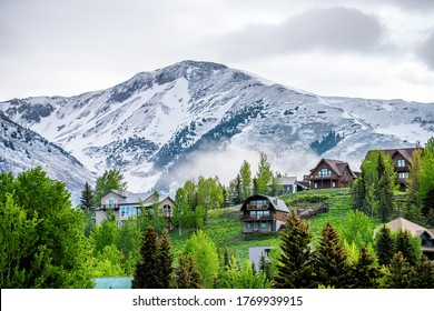 Crested Butte, USA Colorado village in summer with clouds and foggy mist morning and houses on hillside with green trees