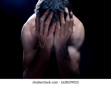 crestfallen or depressed half naked white or caucasian young  man with hands in head  covering his face with zenith lightning in a dark room or black background.