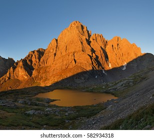 Crestone Peak in early morning orange light reflected in South Colony Lake