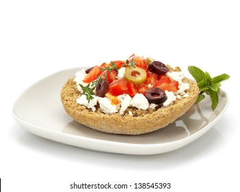 cretan(greek) typical plate with a slice of roasted barley bread, goat cheese, olives, tomato, herbs and olive oil