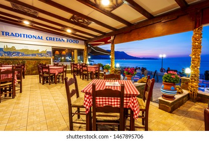 Crete, Greece - April 25 2018: Traditional Cretan Food Restaurant at Paraliaki promenaad at sunset in Kissamos, Crete, Greek Islands, Greece, Europe