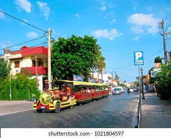Crete, Greece - August 20, 2017: Bright red-yellow little tourist train with people on tourist resort of Platanias. Cheerful entertainment, easy trips.