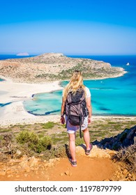 Crete, Greece: Blonde beautyful girl walking along the Balos beach with backpack and enjoying beautiful views. Lagoon of Balos is one of the most visited tourist destinations on west coast of Crete.