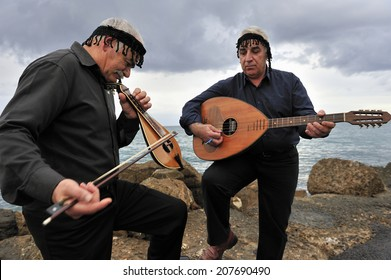 CRETE, GREECE, January. 28. 2009: musician playing Cretan lute and lyre, traditional instrument, of Crete, at the fort of Heraklion, Crete, Greece