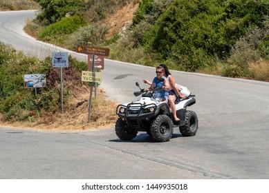 Crete, Greece. June 2019. Couple riding a quad bike on a country lane at Rodopos near Kissamos, eastern Crete,