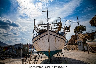Crete / Greece - September 27, 2018: Old fishing boat on the shore. A ship pulled ashore. Harbor in the village of Hersonissos on the island of Crete, Greece.