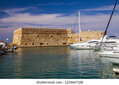 Crete, Heraklion / Greece - September 27, 2018: Boats and motorboats under the walls of Koules Fortress in Heraklion.Fortress on the sea, tourist attraction of the city of Heraklion.