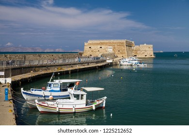 Crete, Heraklion / Greece - September 27, 2018: Fishing Boats under the walls of Koules Fortress in Heraklion. Fortress on the sea, tourist attraction of the city of Heraklion.